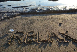 "pic of sandy beach ,written in sand the word ""relax"""